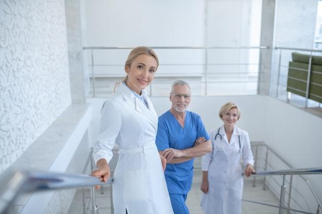 就業日。病院の階段に立っている笑顔の医師のグループ