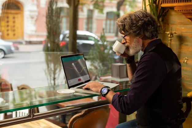 就業日。コーヒーを楽しんで仕事をしているカフェの大きな窓の近くに座っているハンサムなひげを生やした男。