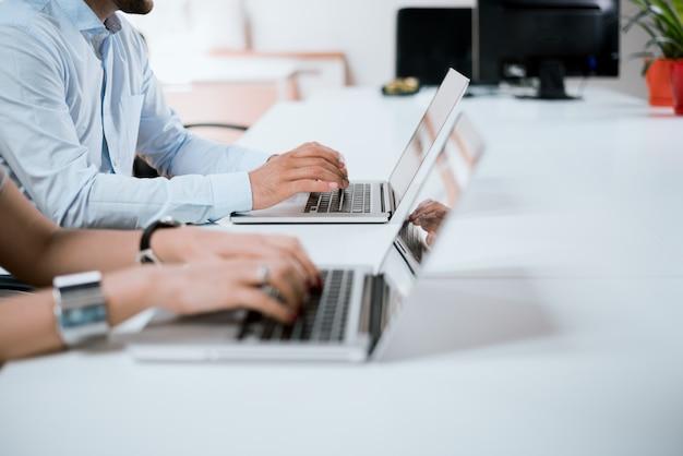 オフィスで働く日。ビジネスマンの手がオフィスのノートパソコンのキーボードで入力します。
