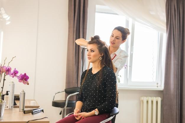 ビューティーサロン内での営業日。美容師はヘアスタイリングをします。