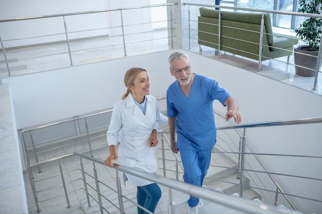 Рабочий день. врачи мужского и женского пола ходят по лестнице, беседуют дружески