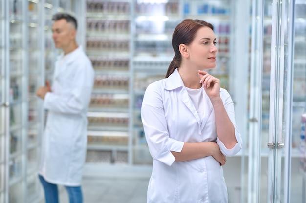 就業日。薬局で薬を持って棚の近くに立っている後ろで忙しい医療用ガウンと男性従業員の物思いにふけるきれいな女性