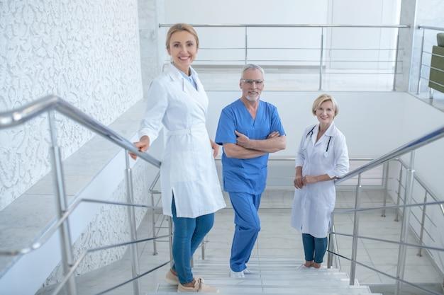 就業日。病院の階段に立っている笑顔の医師のチーム