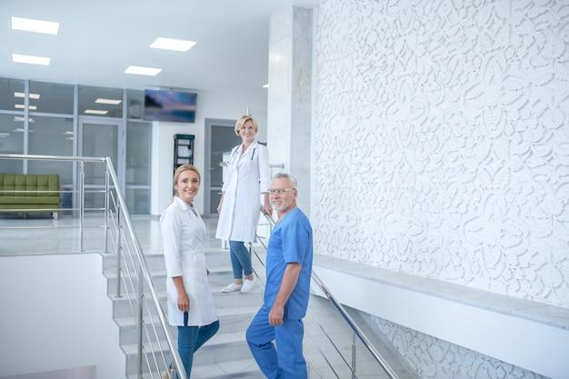 就業日。階段に立っている笑顔の医師のチーム