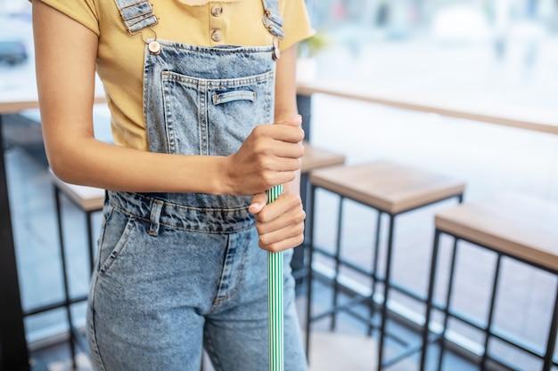 Рабочий день. руки женщины в джинсовом комбинезоне держат швабру в кафе, лица не видно
