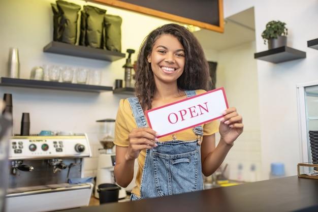 就業日。開いていると言う看板を保持しているカフェのバーカウンターの後ろに立っている若い幸せな女性