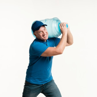 Working delivery man holding water bottle