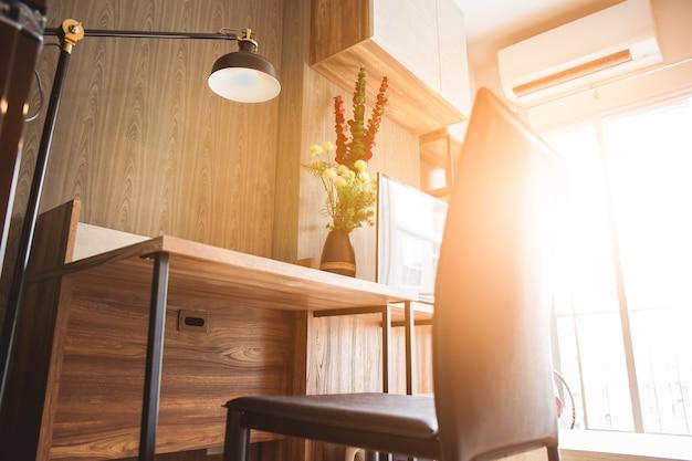 기어 오르는 햇빛을 가진 거실에서 독서 용 램프가있는 책상과 의자