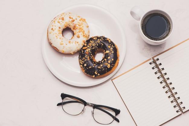 デザートとコーヒーのあるワーキングデスク。大理石のテーブルトップにエスプレッソのカップが付いたケーキドーナツ。