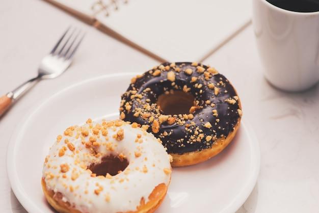 디저트와 커피가 있는 업무용 책상. 대리석 테이블 위에 에스프레소 한 잔을 넣은 케이크 도넛.