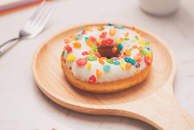디저트와 커피가 있는 업무용 책상. 대리석 탁자 위에 에스프레소 한 잔을 얹은 글레이즈드 도넛.