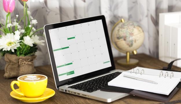 ノートパソコンとノートブック、ラテコーヒー1杯を備えたワーキングデスク