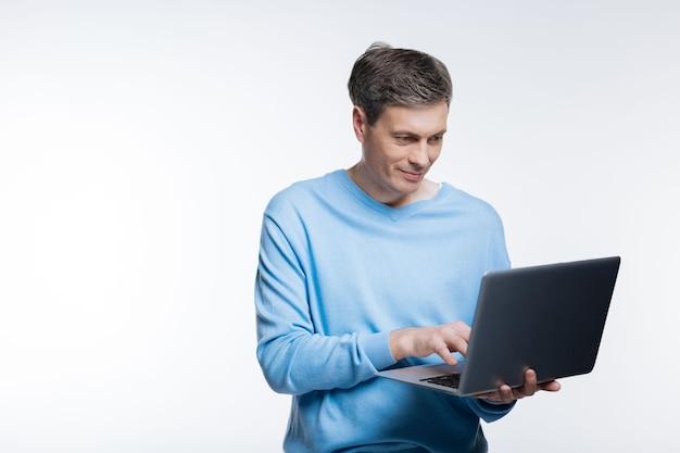 勤勉に働きます。ラップトップで作業し、灰色で何かを入力している青いプルオーバーの快適な中年男性