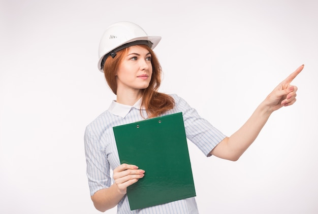 Работа, инженерия, концепция людей - молодая красивая рыжая женщина в шлеме архитектора с документами, показывающими новый проект.