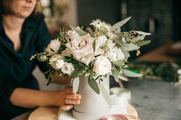 꽃집의 작업 환경, 플로리스트는 신선한 흰색 장미 꽃다발을 만들기 위해 노력하고 있습니다. 취미 또는 소규모 비즈니스 개념