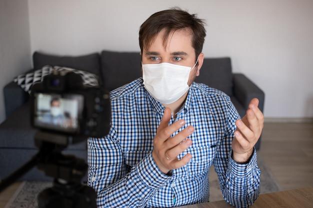 あなたのために働いています。ビデオを作るマスクの素敵なコンテンツの若い男。社会的距離の封じ込め自己検疫のために家にいる