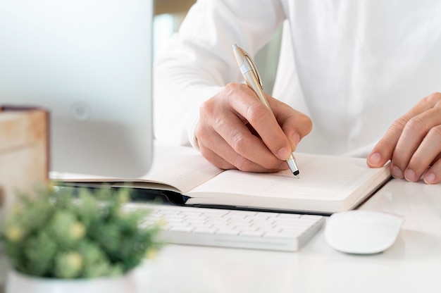 Working form home concept, closeup view of man writing on notebook.