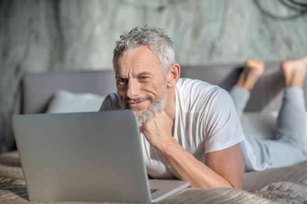 Работать из дома. улыбающийся седой мужчина за компьютером, лежа в постели