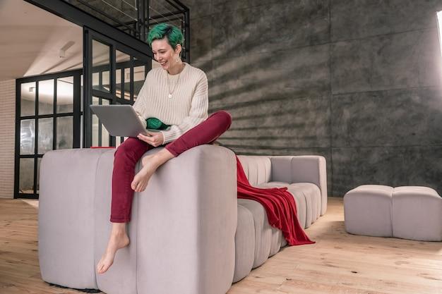 家で働く。ベージュのセーターと素敵なズボンを着た緑の髪の女性が在宅勤務
