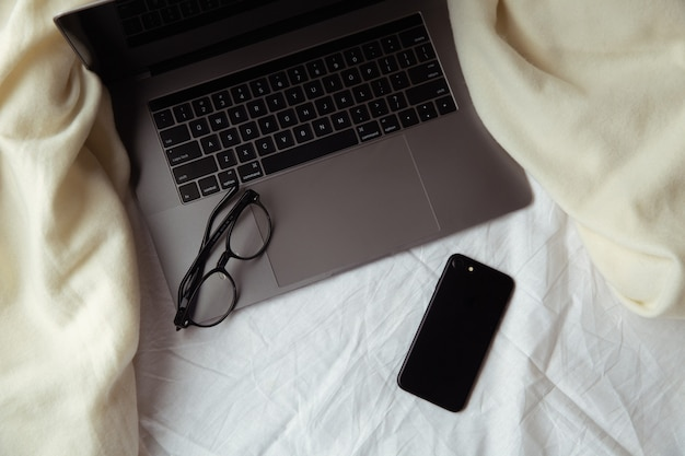 재택 근무. 노트북과 흰색 침대에 안경입니다. 집에서 일하는 개념