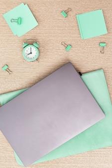 재택 근무. 업무용 노트북과 매일 제어 시간을위한 시계.