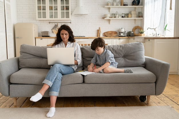 在宅勤務の母親のフリーランサーは、小さな息子の絵と一緒にソファに座ってラップトップコンピューターを使用します