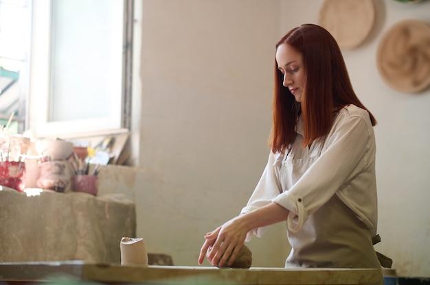 Работающий. рыжий милый гончар работает в своей мастерской и выглядит вовлеченным