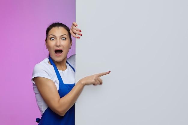アジアの外観の青いエプロンで働く女の子は、白いビルボードでポーズをとります。広告の概念