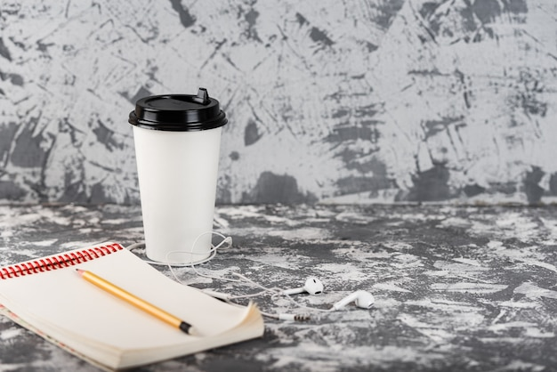 Working on go. coffee cup and notepad on grey stone table.