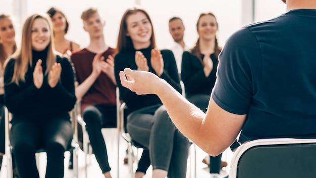 Рабочая группа аплодирует бизнес-спикеру во время встречи