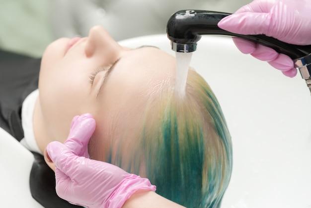 미용실에서 일하는 미용사. 헤어스타일리스트는 특수 세면대에 있는 샤워실에서 샴푸로 머리를 씻습니다.