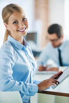 Working hard to become successful. smiling young businesswoman in formalwear holding digital tablet and looking at camera while her male colleague working in the background