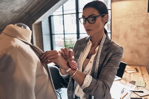 Усердно работаем для достижения наилучших результатов. серьезная молодая женщина в очках, используя швейные иглы для шитья куртки на манекене, стоя в своей мастерской