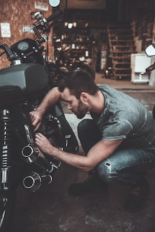 Working in his garage. confident young man repairing motorcycle near his garage