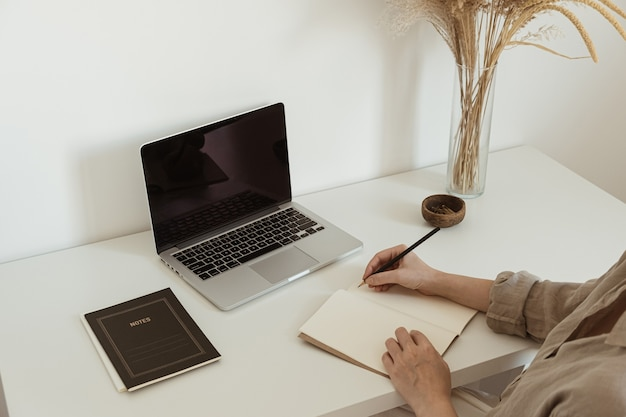 Working at home concept. aesthetic minimalist workspace background. young woman write notes in notebook.