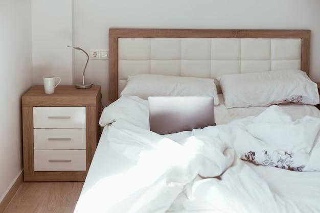 家で働く。作られていないベッドのラップトップ。快適で居心地の良いリモートホームオフィス。