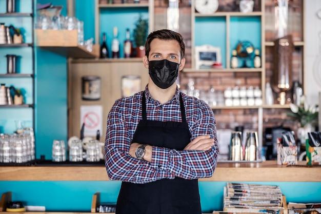 レストランでの作業とコロナウイルスのパンデミック。レストランのバーの前に立っている男性のクローズアップショットは、格子縞のシャツと保護用マスクを着用しています。腕時計と腕を組む、腰を上げる