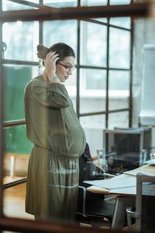 Работаем в корпорации. беременная преуспевающая деловая женщина чувствует себя занятой работой в своей корпорации