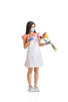 Работаем в маске для лица. молодая красивая женщина, флорист с красочным свежим букетом, изолированным на белом фоне студии. кавказская женщина, работник современного искусства. финансы, экономика, профессиональная деятельность.