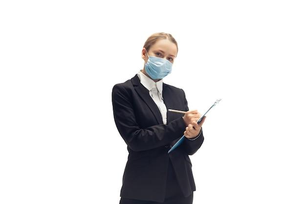 フェイスマスクでの作業。若い女性、会計士、金融アナリスト、または白いスタジオの壁に隔離されたオフィススーツのブッカー。