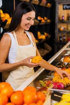 フルーツパラダイスで働いています。さまざまな果物を背景に食料品店で働くエプロンの美しい若い女性