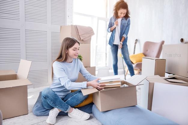 調和して働く。ルームメイトが本を開梱している間、モップで床を掃除している明るい少女