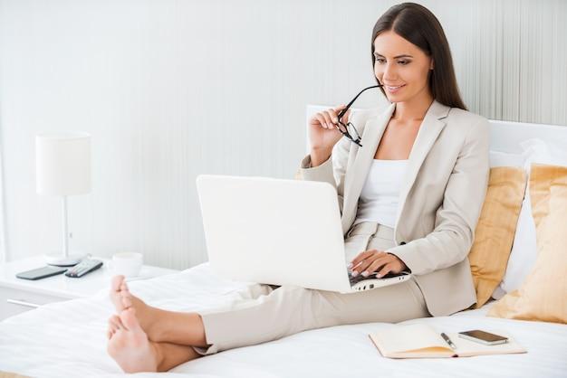 Работа в гостиничном номере. красивая молодая деловая женщина в костюме работает на ноутбуке и улыбается, сидя в постели в гостиничном номере