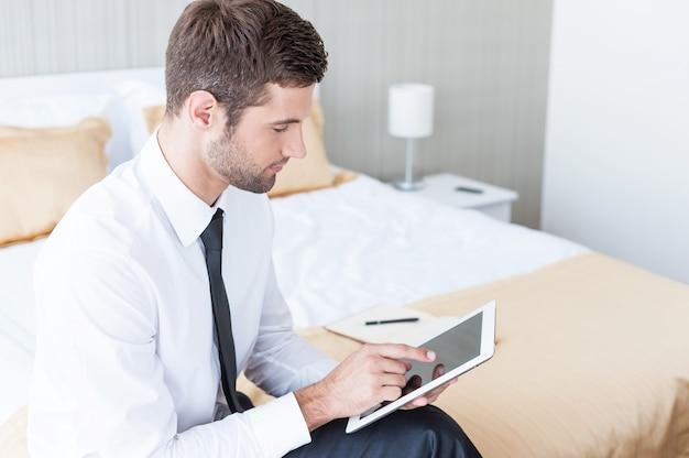 Работа в гостиничном номере. уверенный молодой бизнесмен в рубашке и галстуке, работающий на цифровом планшете, сидя на кровати в гостиничном номере