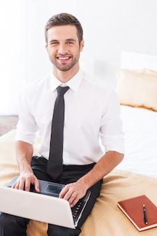 Работа в гостиничном номере. вид сверху красивого молодого человека в рубашке и галстуке, работающего на ноутбуке и улыбающегося, сидя на кровати в гостиничном номере
