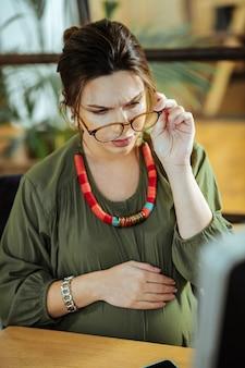 Работа в офисе беременная женщина в блузке цвета хаки надевает очки во время работы в офисе