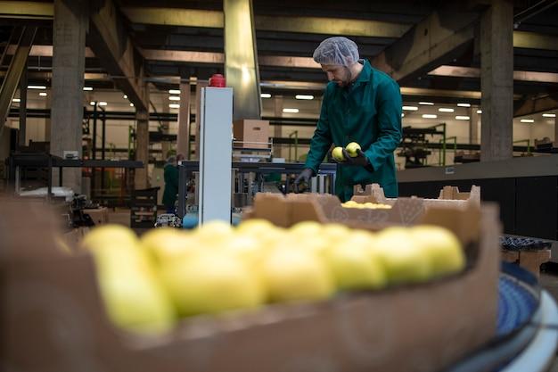 유기농 식품 공장에서 녹색 사과를 분류하고 냉동 창고로 운반하는 컨베이어 벨트에서 일합니다.