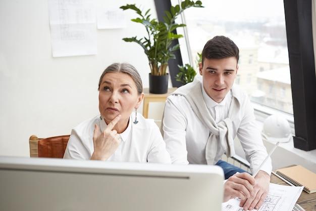 팀에서 일하고 있습니다. 창조적 인 건축가 젊은 남자와 수석 여자, 흰색 사무실에서 건설 계획을 개발, 컴퓨터 앞에 책상에 앉아 사려 깊은 표정을 갖는, 브레인 스토밍