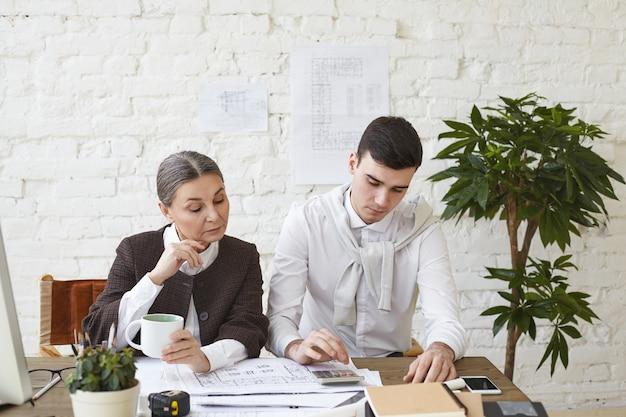 チームでの作業。彼の白髪の女性の上司と一緒にオフィスに座って、彼らの前で図面を勉強している計算機を使用して計算を行う真剣に焦点を当てた若い滑らかに剃られた男性建築家