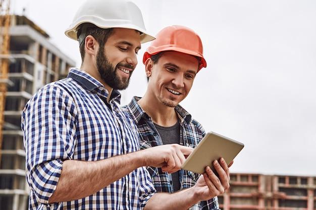Два молодых и веселых строителя в защитных касках работают в команде и используют цифровой планшет.